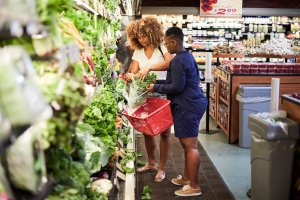 Black women shopping for produce in grocery store