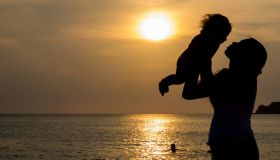 Silhouette Of Female Holding Little Girl At Sunset Sun Reflection In Sea Surface