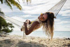 Happy woman relaxing in hammock on the beach.