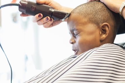 Hairdresser clipping hair of boy in retro barbershop