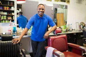 Black barber smiling in retro barbershop