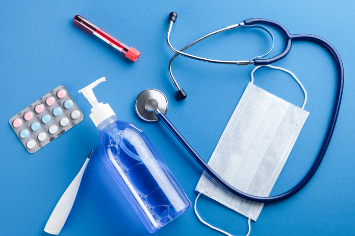 Medical disposable mask, thermometer, hand sanitizer, stethoscope, tablets, blood in a test Tube on a Blue Background.