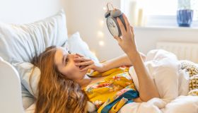 Worried and sick blond young woman in bed late in the morning, overslept looking at the alarm clock ad late for work or school