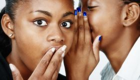 It's a scandal! Beautiful young woman whispers gossip to her friend, who looks shocked