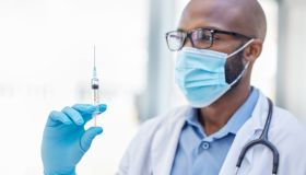 Shot of a young doctor holding a syringe filled with liquid at work